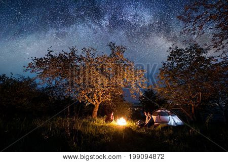 Three tourists sitting at a campfire near tent under trees and beautiful night sky full of stars and milky way. Night camping. Astrophotography