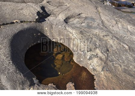 A giant's kettle or Pothole in a stone created by the streaming water in the Pite river picture from the North of Sweden.