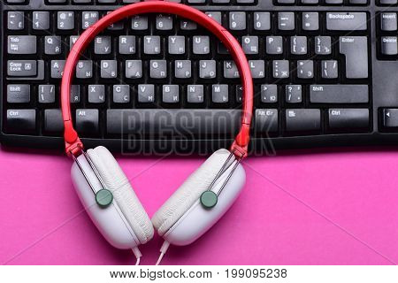 Headphones And Black Keyboard. Electronic Appliances On Pink Background