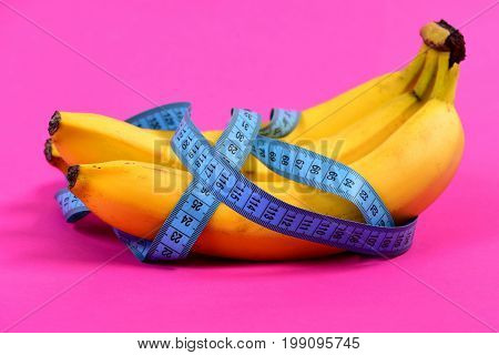 Bunch Of Bananas Wrapped Around With Blue Tape For Measuring
