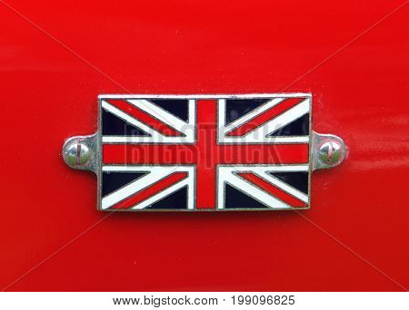 Union Jack metal badge detail on a vintage red sports car
