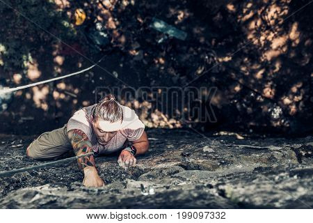 Concentrated Male Climber Climbs A Steep Rock. Extreme Lifestyle Outdoor Activity Concept
