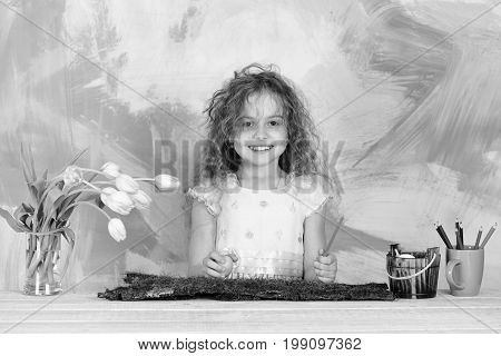 happy easter traditional spring holiday decoration girl painter small child with curly hair painting egg in bucket with pencil tulip flowers in vase on colorful background. womens or mothers day