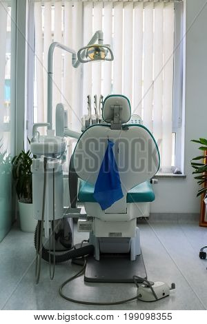 Blue and white dentist chair with sink and dentist equipment tools in dental clinic practice with bright light blue towel and plant