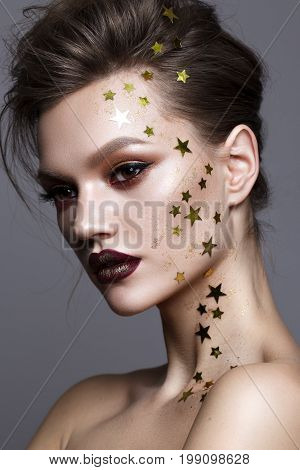Close up portrait of beautiful young model with evening makeup and a lot of golden stars on her face, perfect skin, volume hairdo. Trendy colorful smoky eyes and lips. Art makeup
