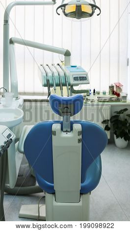 Blue and white dentist chair with sink and dentist equipment tools in dental clinic practice