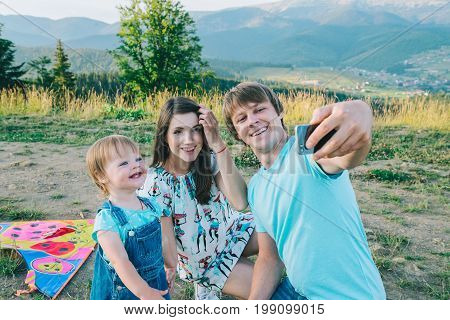 happy young family taking selfie while playing with kite outside