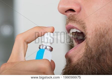 Close-up Of A Man's Hand Spraying Breath Freshener