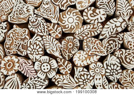 Indian background. Leaf, flower patterns, sun symbols on wooden texture of print blocks for traditional asian textile clothing.