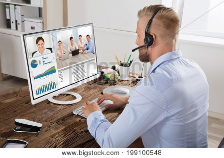 Smart Businessman Video Conferencing With Team On Computer At Workplace