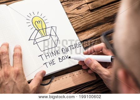 Businessman Drawing The Think Outside The Box Concept Chart On Notebook With Black Marker