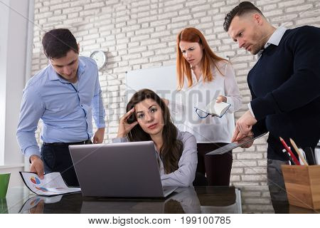 Young Worried Business Woman With Her Angry Colleague In Office