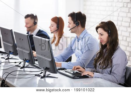 Team Of Young Customer Support Phone Operators Working In Office