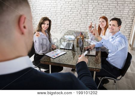 Businessman Asking Question To His Colleagues During Presentation In Office