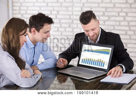 Financial Advisor Showing Investment Projection Graph On Laptop To Couple