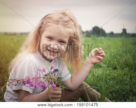 Portrait of cute girl with long blonde hair. Field green grass. The child smiles happily