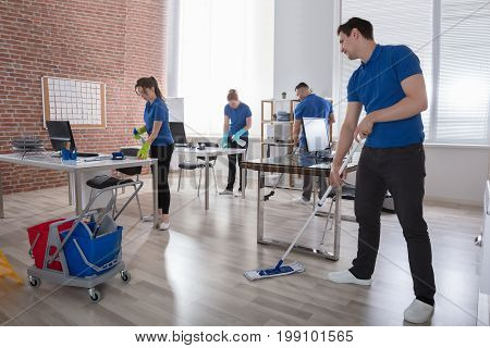 Group Of Janitors Cleaning The Modern Office With Caution Wet Floor Sign
