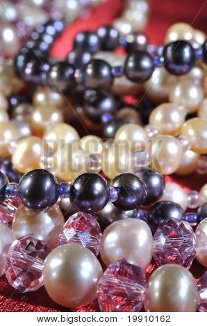 Pearl necklace on a red silk close up poster