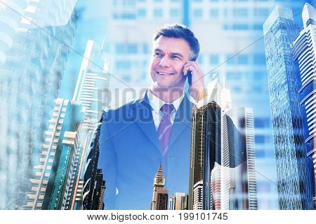 Double exposure of confident businessman talking on mobile phone over city background