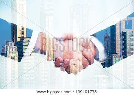 Double exposure of business people shaking hands over city background