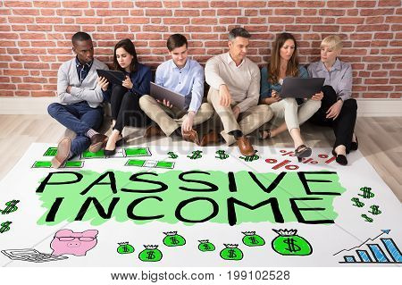 Group Of People Looking AT Passive Income Text On Floor