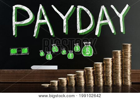 Payday Word On Blackboard Behind Stacked Coins
