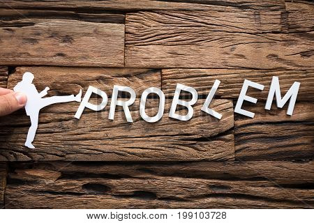 Closeup of hand holding paper businessman kicking word problem on wood