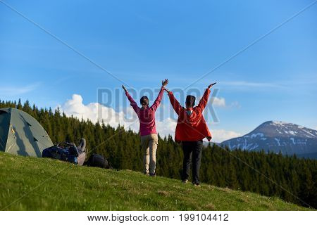 Rearview Shot Of Two Happy Female Friends Enjoying Fantastic Natural View From The Top Of A Hill Whi