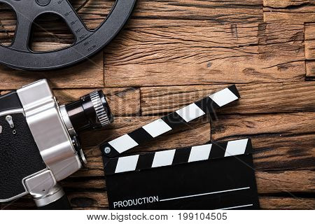 Closeup of movie camera with film reel and clapper board on wood