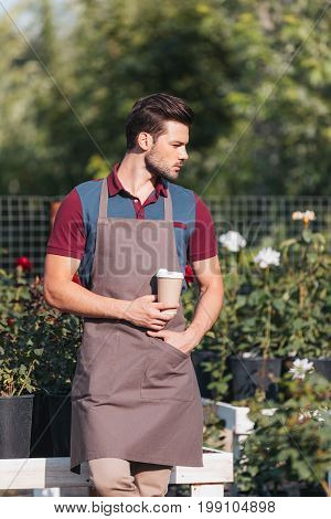 Portrait Of Pensive Gardener With Coffee To Go Looking Away While Standing In Garden