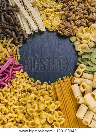 Photo of twelve different pasta types arranged on a slate surface as a frame.