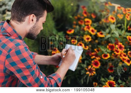 Back View Of Focused Gardener Making Notes In Notebook While Checking Plants In Garden