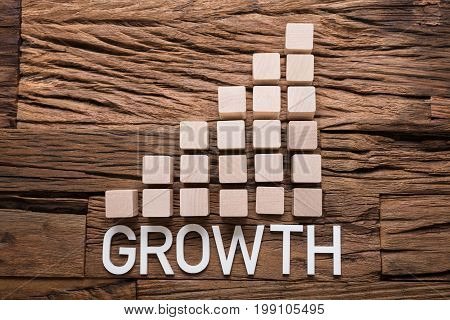Closeup of growth text by increasing bar graph blocks on wooden table