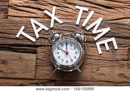 Directly above shot of tax time text by alarm clock on wooden table