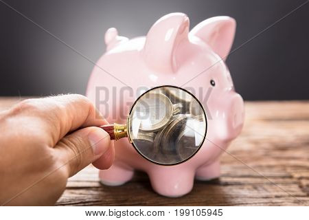 Cropped image of businessman examining coins in piggybank with magnifying glass on wooden table