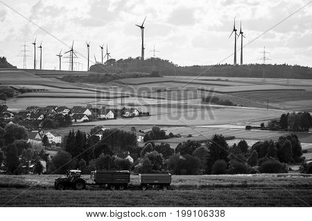 NEUSTADT GERMANY - JULY 30 2017: View of the small town of Neustadt a suburb and surrounding agricultural land and agricultural machinery. Black and white.