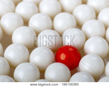 stand out red ball surrounded by white balls. selective focus