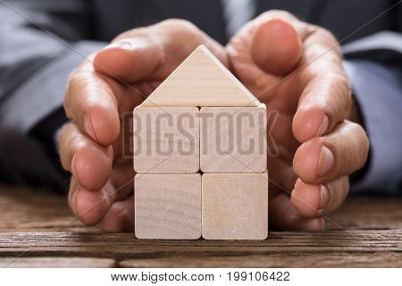 Midsection of businessman covering model home made from wooden blocks with hands at table