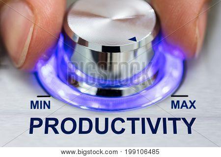 Cropped image of hand turning illuminated metallic knob by productivity text