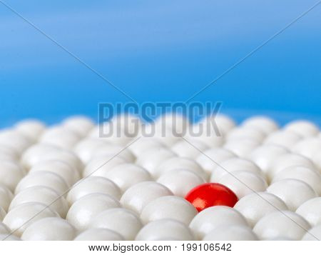 stand out red ball surrounded by white balls on blue background. selective focus