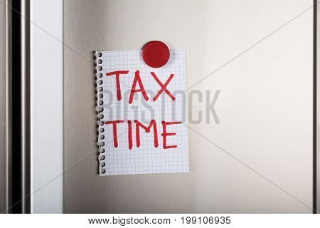 Closeup of tax time note attached with red magnetic thumbtack on metal