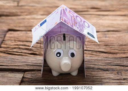 Closeup of piggybank in model home made from euro notes on wooden table