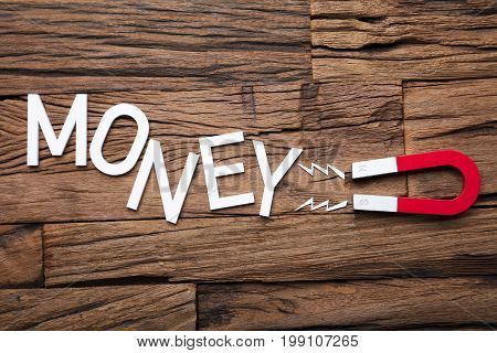Directly above shot of magnet pulling money block text on wooden table