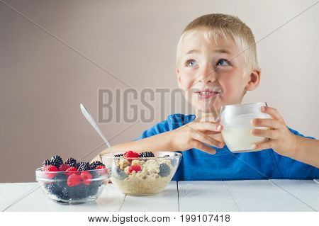 Happy little boy with milk mustache holding glass of milk or yogurt and eating porridge with berries. The concept of a healthy breakfast for children.
