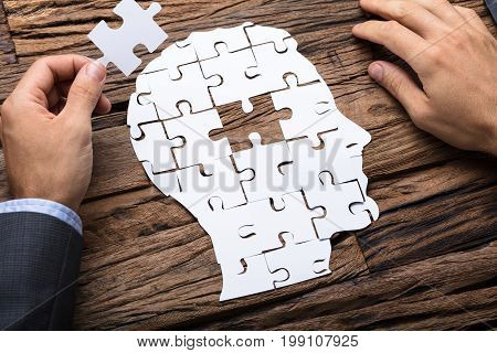 Cropped image of businessman holding paper jigsaw puzzle piece while making head on wooden table