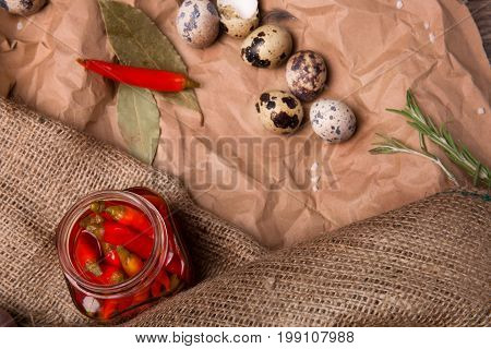 A view from above of green bay leaves, organic rosemary and a few quail eggs on a crumpled paper and on an old cloth. A jar of red peppers, spices and quail eggs on a brown fabric.