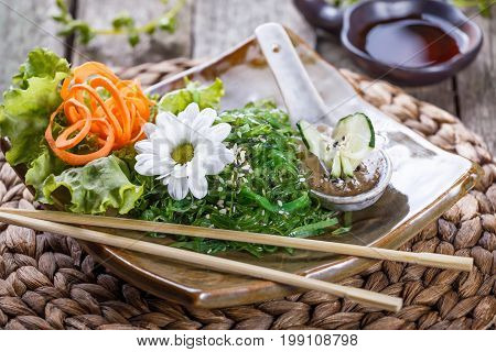 Seaweed Salad wakame in plate with chopsticks on bamboo mat. Japanese Cuisine - healthy sea food