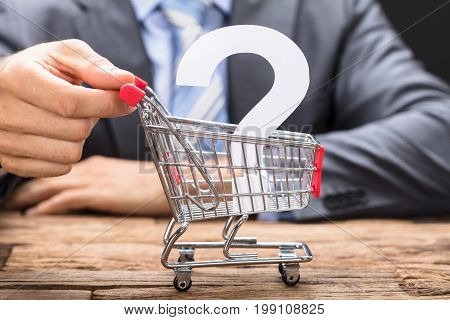 Midsection of businessman pushing question mark in shopping cart on wooden table