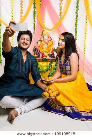 Ganesh Chaturthi - Smart and young Indian couple taking selfie picture or self portrait using smartphone while performing pooja in front of lord ganesh on ganesh festival / utsav, selective focus