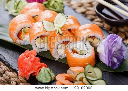 Sushi rolls set with salmon cream cheese red caviar avocado and wasabi on black stone on bamboo mat selective focus. Japanese cuisine